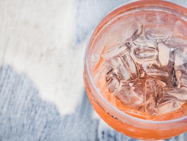 Beau verre avec un cocktail rose et des glaçons