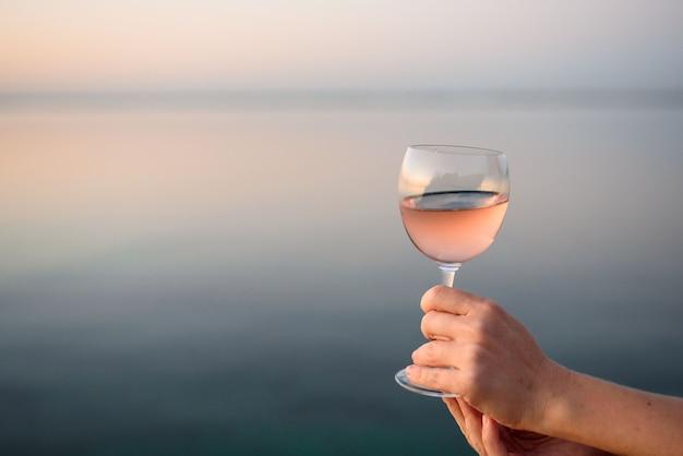 Beau verre à vin rose entre les mains d'une jeune fille. verre de vin au lever du soleil. petit-déjeuner romantique au bord de la mer et du soleil