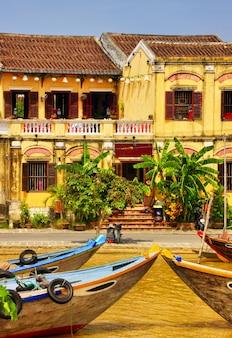 Beau vertical des bâtiments et des bateaux à hoi an, vietnam
