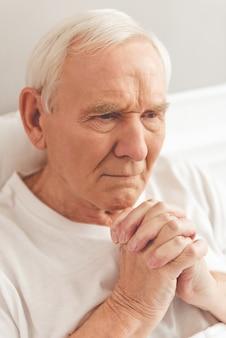 Beau vieil homme prie en position couchée dans son lit à l'hôpital.