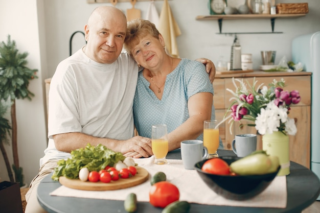 Beau vieux couple prépare des plats dans une cuisine