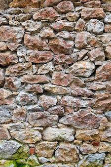 Beau et vieux mur de pierre avec mousse et végétation (mousse, fougères, herbe) faisant face au nord