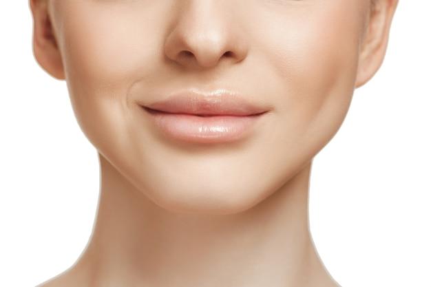 Beau visage féminin. peau parfaite et propre du visage sur blanc.