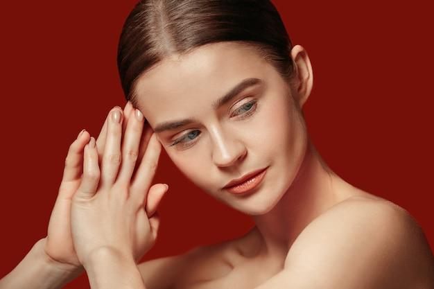 Un beau visage féminin. peau parfaite et propre de jeune femme caucasienne sur fond de studio rouge.