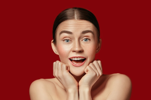 Un beau visage féminin. une peau parfaite et propre de jeune femme caucasienne surprise sur fond de studio rouge.