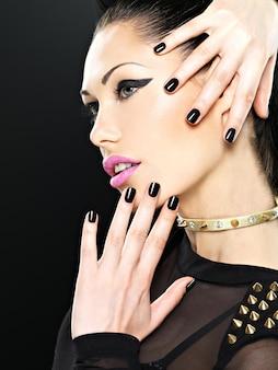 Beau visage de femme fashion avec des ongles noirs et un maquillage lumineux. fille élégante sexy avec des épines de bracelet sur le cou