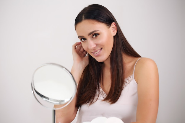 Beau visage de femme gros plan studio sur blanc, brune en chemise de nuit