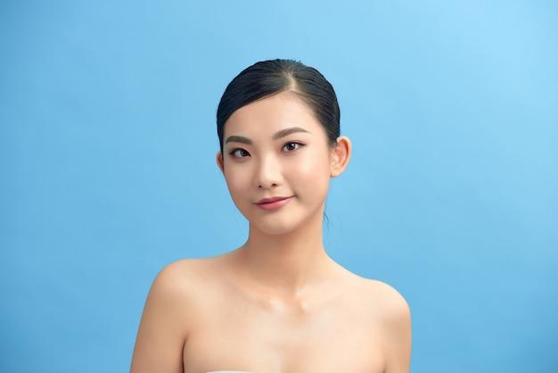 Beau visage de jeune femme adulte avec une peau propre et fraîche et des épaules nues sur fond bleu.