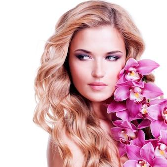 Beau visage de jeune femme blonde avec des poils sains et des fleurs roses près du visage - isolé sur blanc.