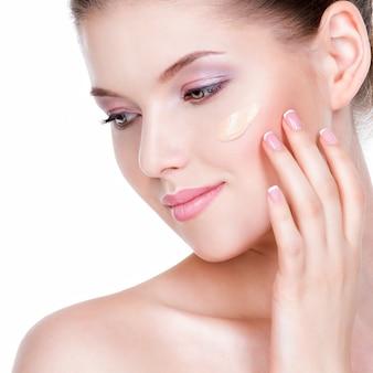 Beau visage de jeune femme avec fond de teint cosmétique sur une peau sur un mur blanc. concept de traitement de beauté.