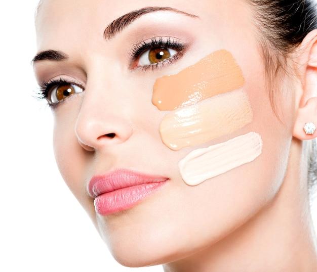 Beau visage de jeune femme avec fond de teint cosmétique sur une peau.