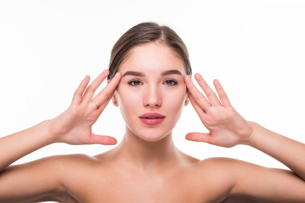 Beau visage de jeune femme à la peau douce et propre isolé sur mur blanc