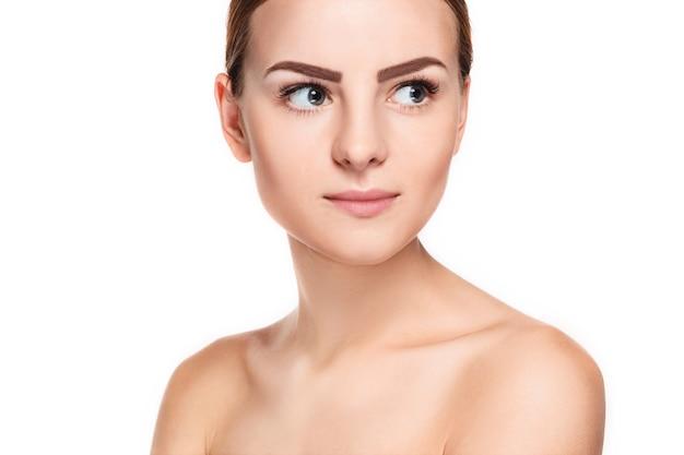Beau visage de jeune femme avec une peau fraîche propre bouchent isolé sur blanc. portrait de beauté. peau fraîche parfaite. modèle de beauté pure. concept jeunesse et soins de la peau