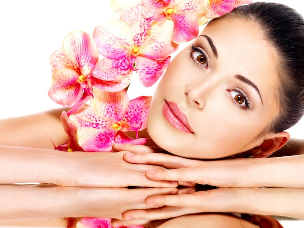 Beau visage de jeune jolie femme avec une peau saine et des fleurs roses- isolé sur blanc
