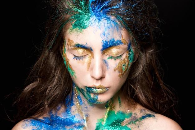 Beau visage avec de la peinture colorée sur un fond noir