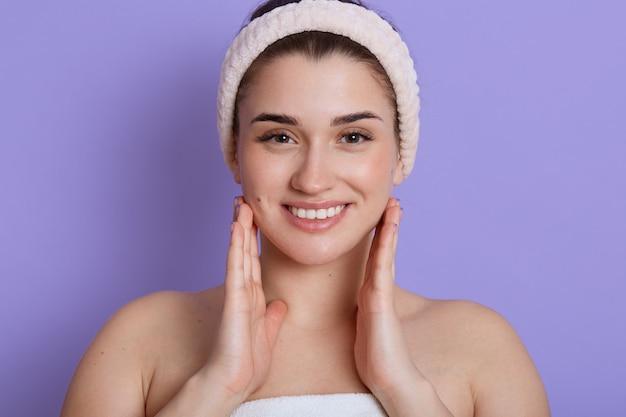Beau visage portrait de jeune femme touchant ses joues et souriant tout en regardant directement, debout avec les épaules nues et porte un bandeau de cheveux. soins de la peau et santé.