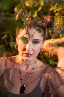 Beau visage. portrait d'une jolie femme sérieuse debout sous l'arbre