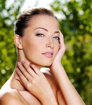 Beau visage sexy d'une jeune femme avec une peau fraîche et saine. femme posant sur la nature. modèle caressant son corps.