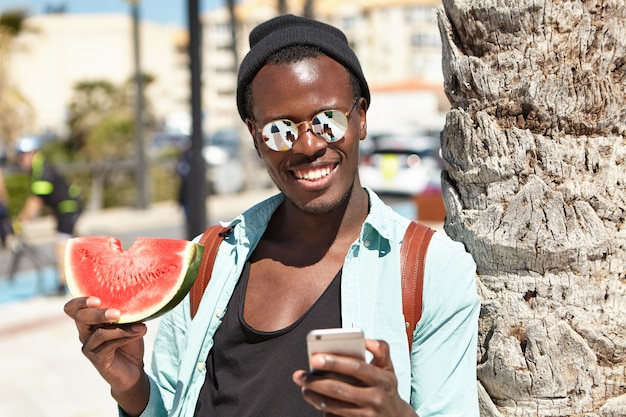 Beau voyageur noir insouciant dans des vêtements urbains élégants posant pour selfie, debout à l'extérieur avec une tranche de pastèque, appuyé en arrière sur un palmier, l'écran du téléphone se reflète dans ses abat-jour en miroir