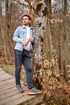 Beau voyageur de race blanche debout avec un thermos à côté d'un arbre dans la forêt, vêtu de façon décontractée, lors d'une randonnée, d'un voyage, d'une aventure. l'homme barbu se repose, boit du thé. espace de copie