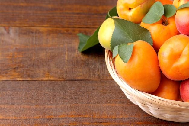 Beaucoup d'abricot frais et mûr dans un panier en osier sur un fond en bois marron