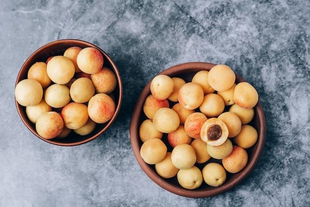 Beaucoup d'abricots jaunes mûrs se bouchent dans une vaisselle sur la table 1