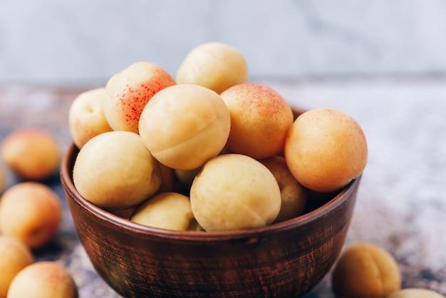 Beaucoup d'abricots jaunes mûrs se bouchent dans une vaisselle sur la table