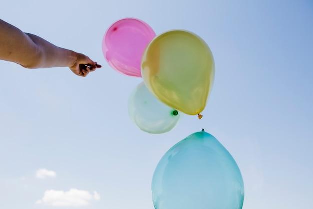Beaucoup de ballons colorés dans la main contre le ciel bleu