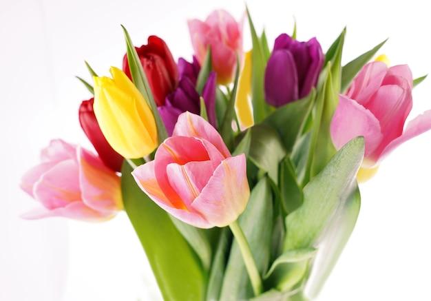 Beaucoup de belles tulipes colorées avec des feuilles dans un vase en verre isolé sur une surface transparente