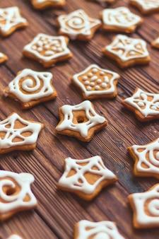Beaucoup de biscuits en pain d'épice en forme d'étoile avec glaçage blanc