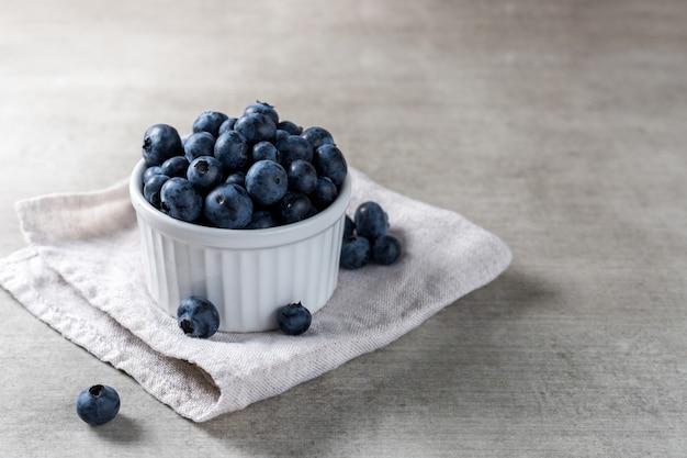 Beaucoup de bleuets frais délicieux sur un pot blanc sur une table en bois.