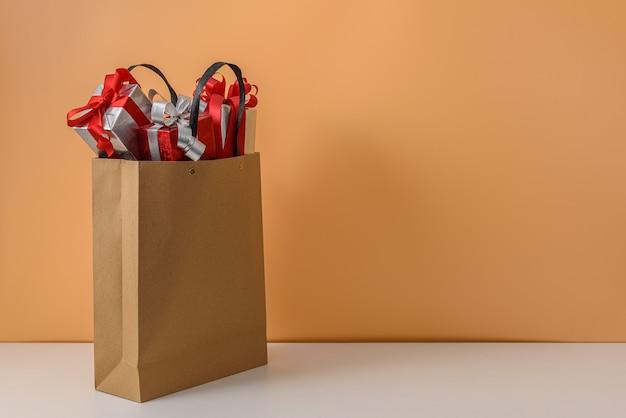 Beaucoup de boîte-cadeau avec noeud de ruban rouge dans un sac à provisions en papier brun. cadeaux de noël ou de noël