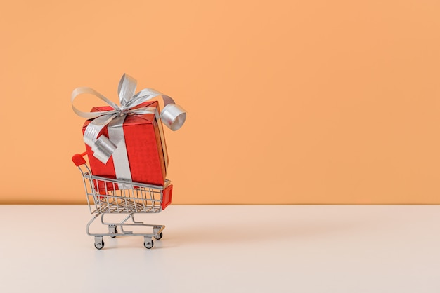 Beaucoup de boîte-cadeau avec noeud de ruban rouge et panier ou chariot sur tableau blanc et fond orange pastel