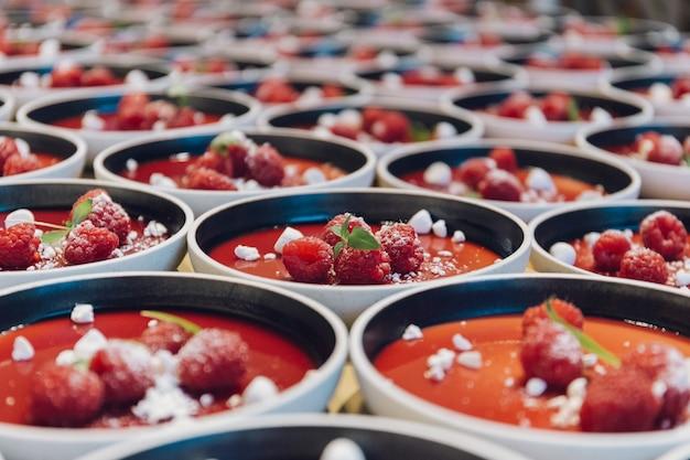 Beaucoup de bols avec un dessert rouge à base de framboises et de levure chimique