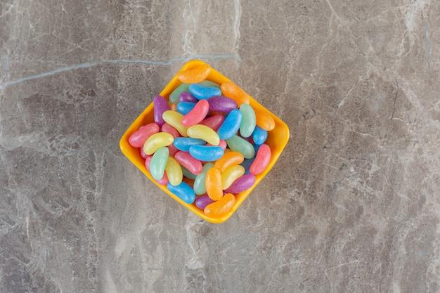Beaucoup de bonbons sur un bol orange sur une surface grise.