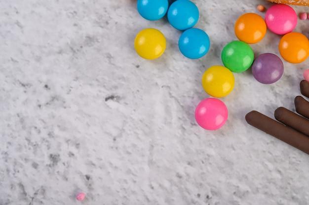 Beaucoup de bonbons multicolores placés sur une surface blanche.