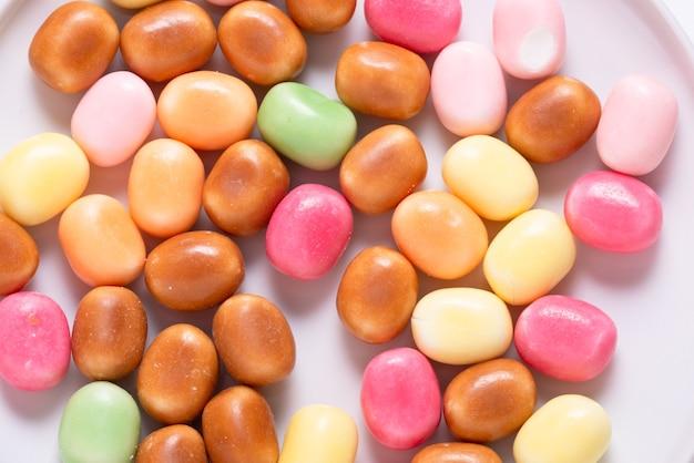 Beaucoup de bonbons sucrés lumineux, fond coloré