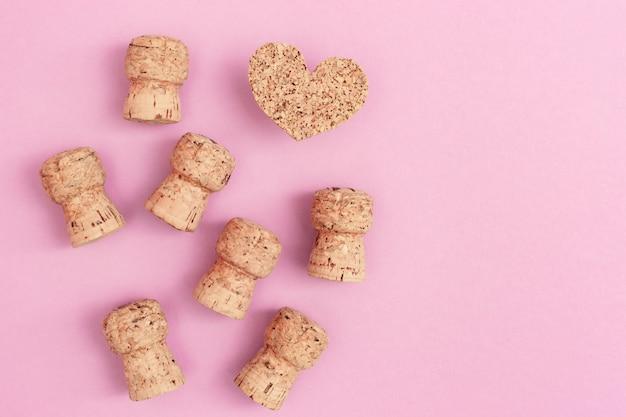 Beaucoup de bouchons de champagne et coeur sur fond de papier rose avec espace copie. mise à plat pour anniversaire, fête, mariage. invitation fête poule.