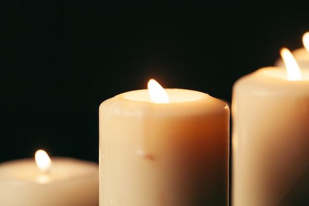 Beaucoup de bougies allumées la nuit. beaucoup de flammes de bougie rougeoyantes