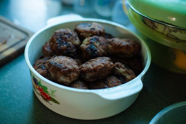 Beaucoup de boulettes de viande frites prêtes à l'emploi se trouvent dans une grande casserole en aluminium blanc sur la table