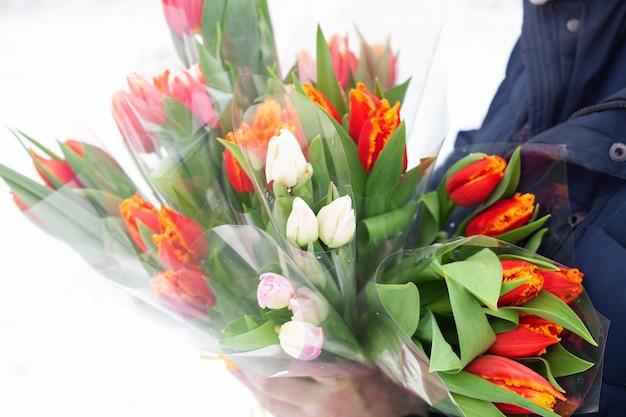 Beaucoup de bouquets de tulipes colorées entre les mains des hommes. félicitations pour les vacances.