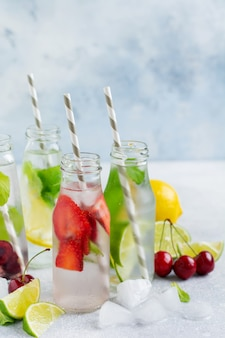 Beaucoup de bouteilles avec de la limonade d'été rafraîchissante au citron vert, fraise, cerise, concombre et glace sur fond de béton gris.