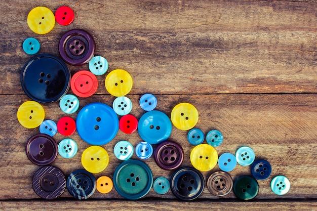 Beaucoup de boutons colorés pour des vêtements sur bois