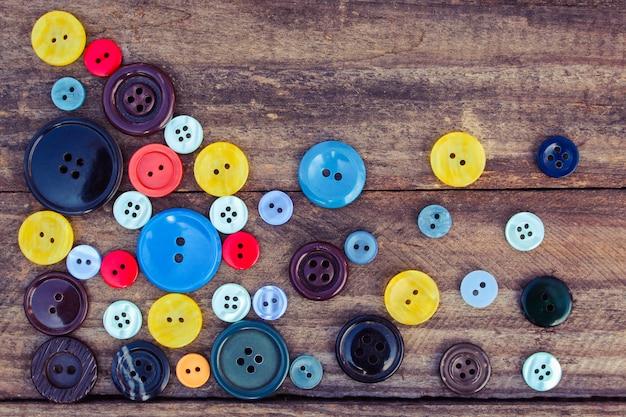 Beaucoup de boutons colorés pour les vêtements sur fond en bois
