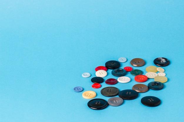 Beaucoup de boutons de couleur sur une surface bleue.