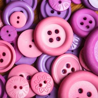 Beaucoup de boutons de couture roses et violets en gros plan