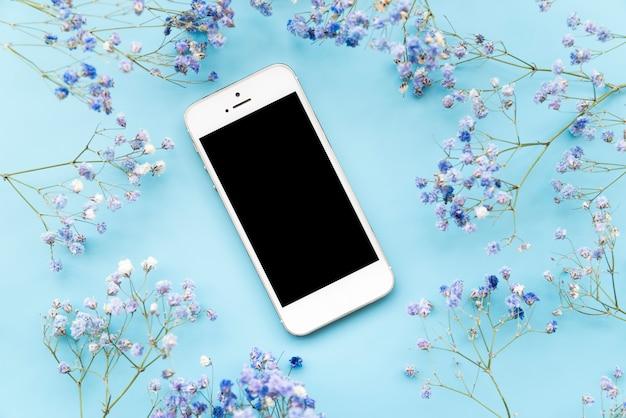 Beaucoup de brindilles de fleurs fraîches avec smartphone