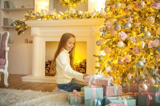 Beaucoup de cadeaux. jolie fille blonde regardant occupé à regarder les cadeaux de noël