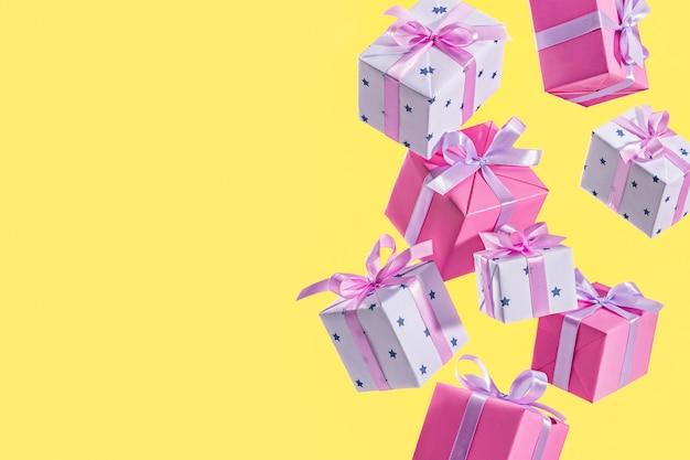 Beaucoup de cadeaux tombant du ciel sur une surface jaune