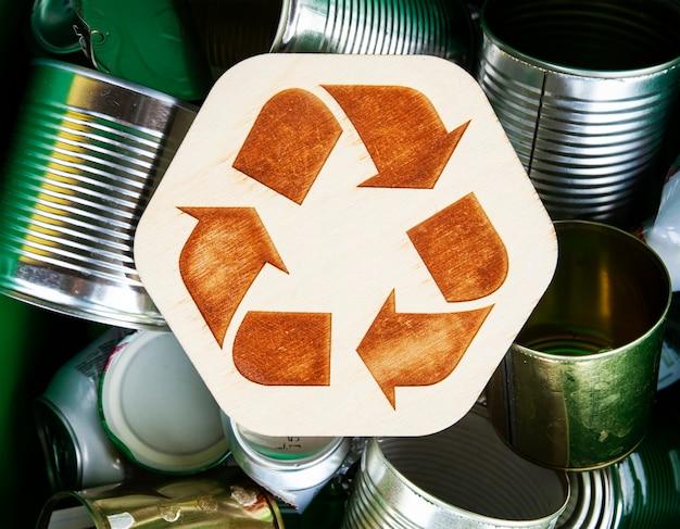 Beaucoup de canettes dans la poubelle dans l'icône de recyclage entre elles